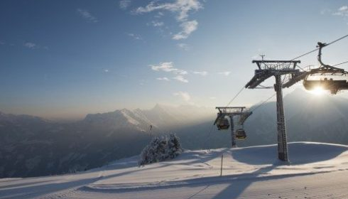Penkenbahn cable car in late afternoon sun in Marhofen, Austria - slopes covered in snow
