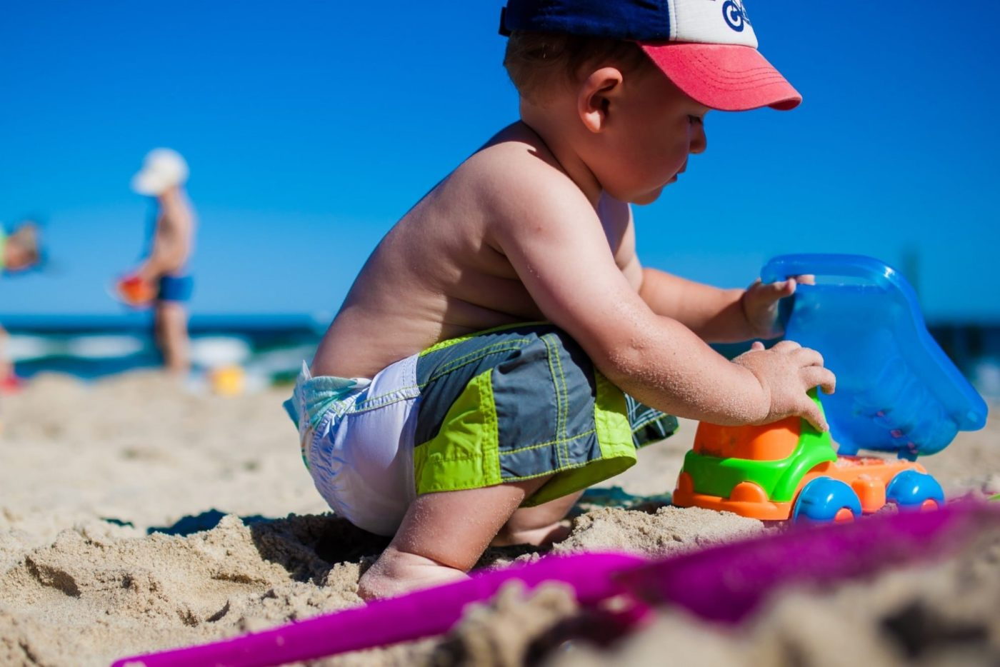 Boy on the beach playing with toys