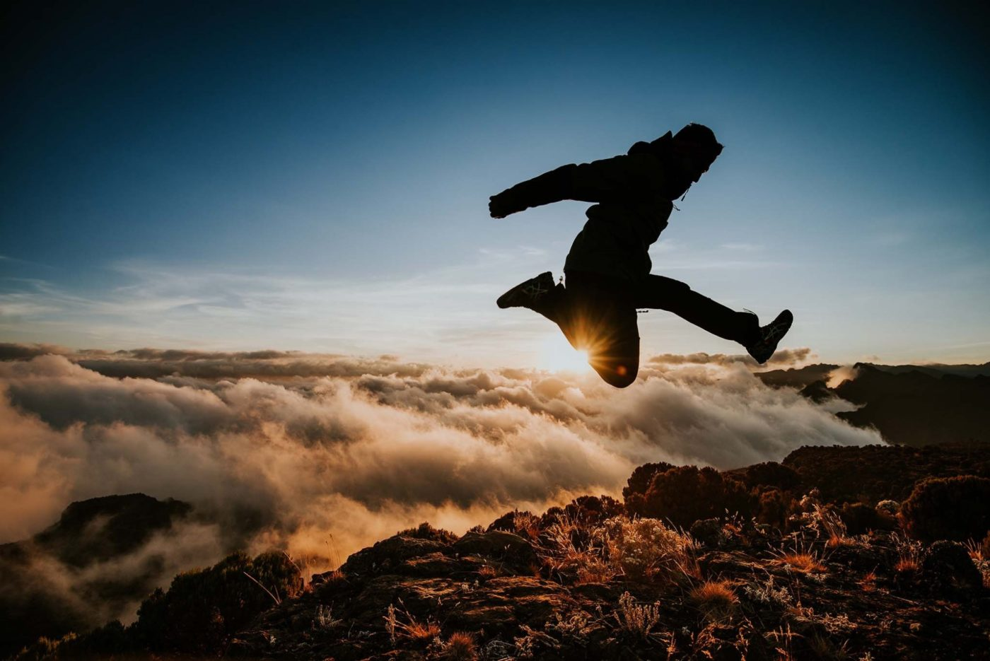 Picture of a man jumping above the clouds on Kilimanjaro