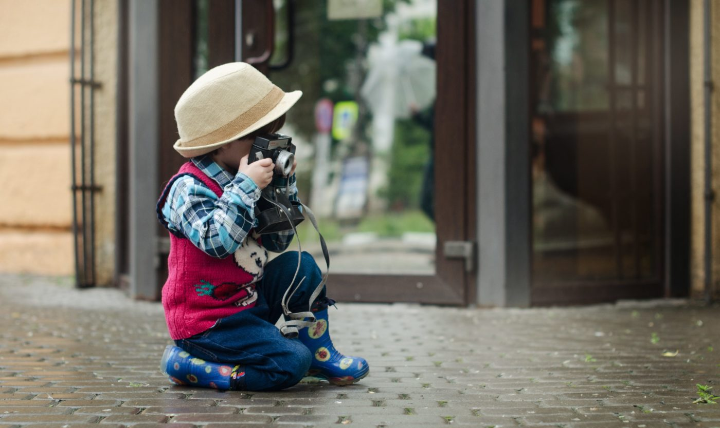 city break: boy kneeling on the pavement taking photos