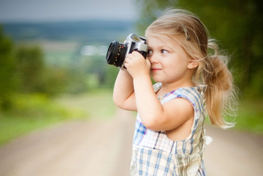 little girl taking photo on road trip