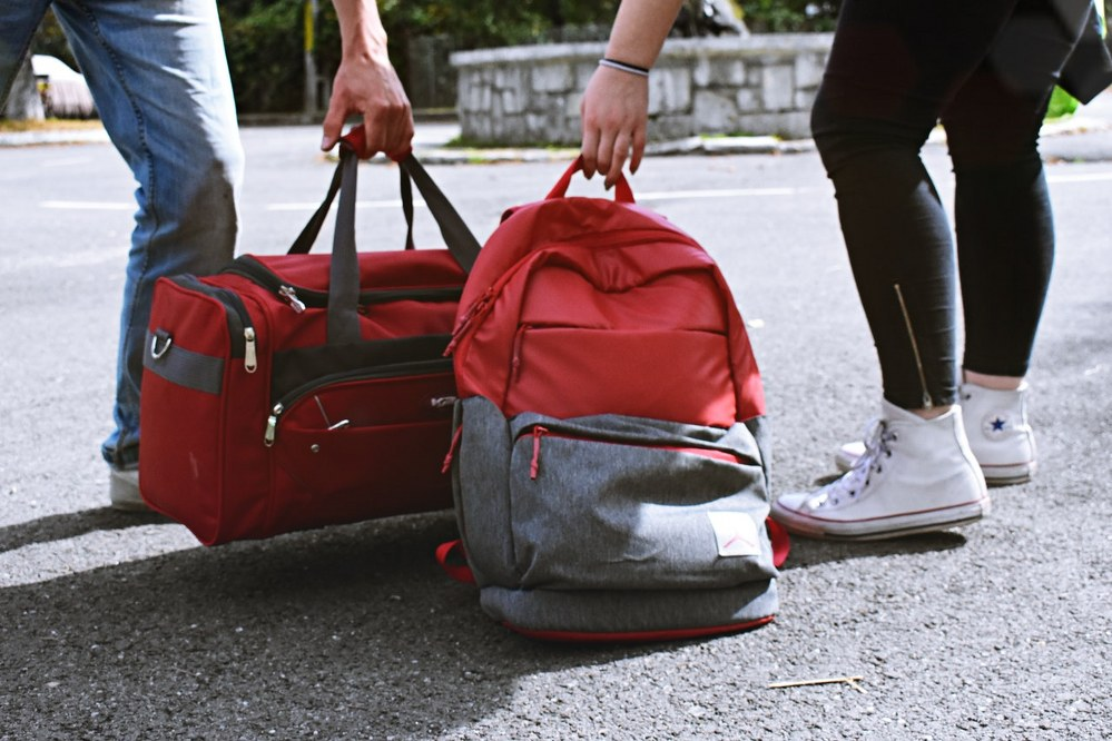 single mum holidays - woman accepts help with luggage
