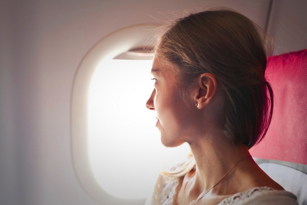 flying with kids - mum looking out of plane window