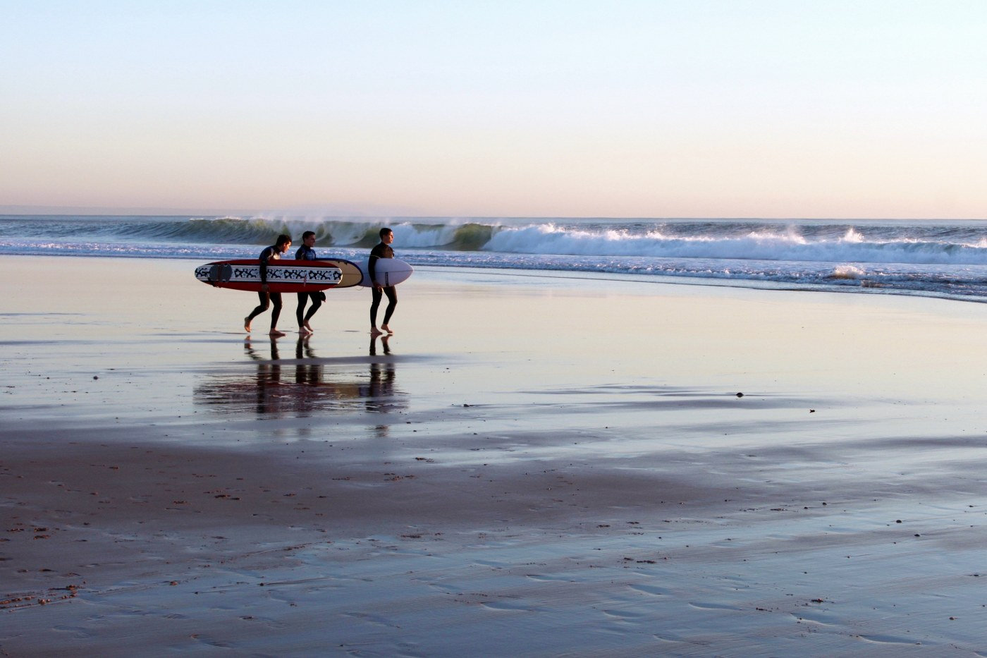 single parent holidays with teenagers - young surfers carrying board