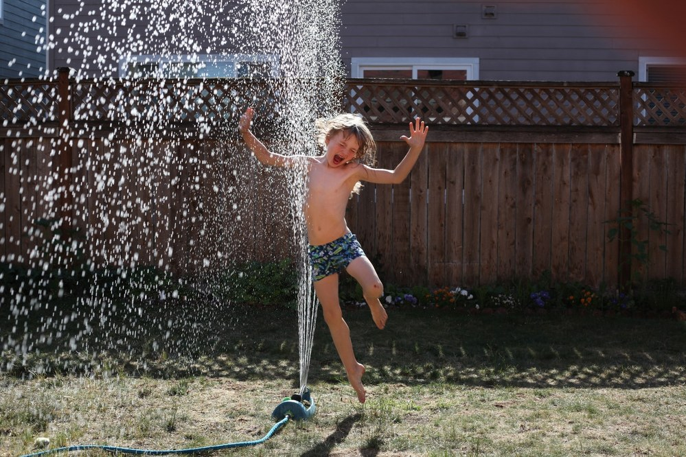 family activities - boy playing with sprinkler in garden