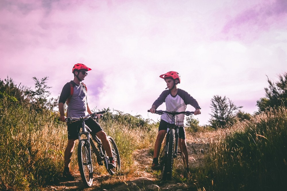 how to bond with kids on holiday - father and son cycling together
