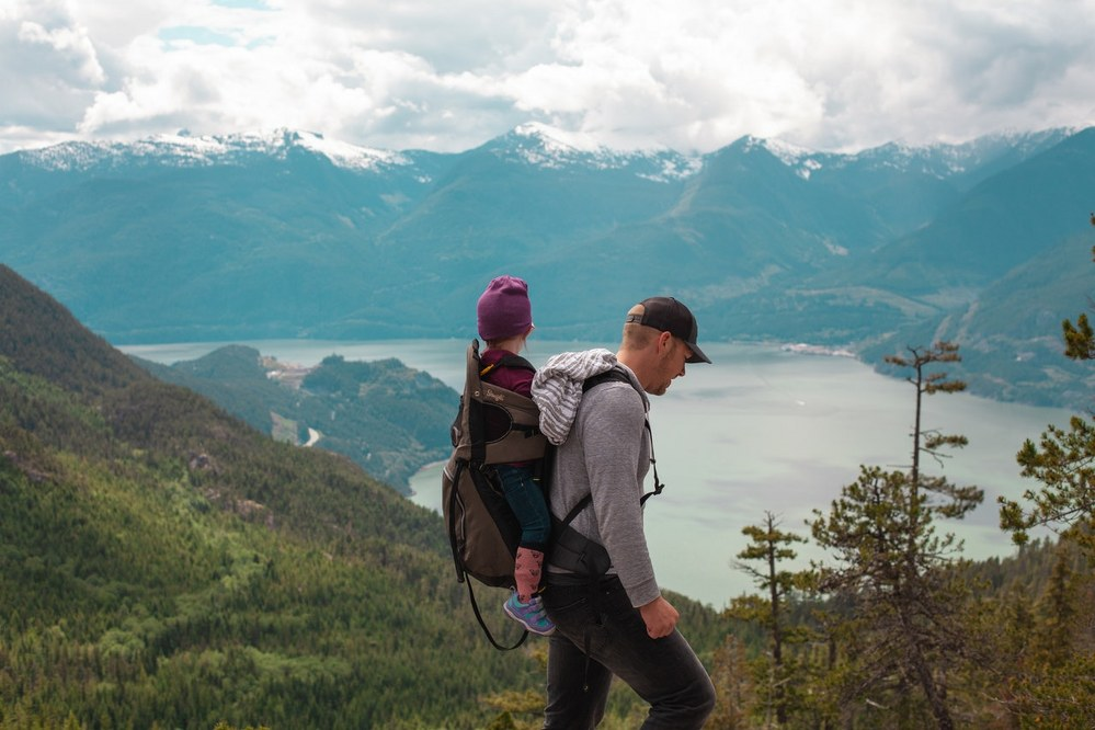 how to bond with kids on holiday - dad with daughter on backpack