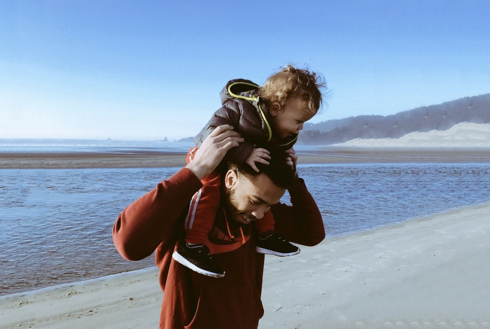 small families - dad and child on shoulders by the beach