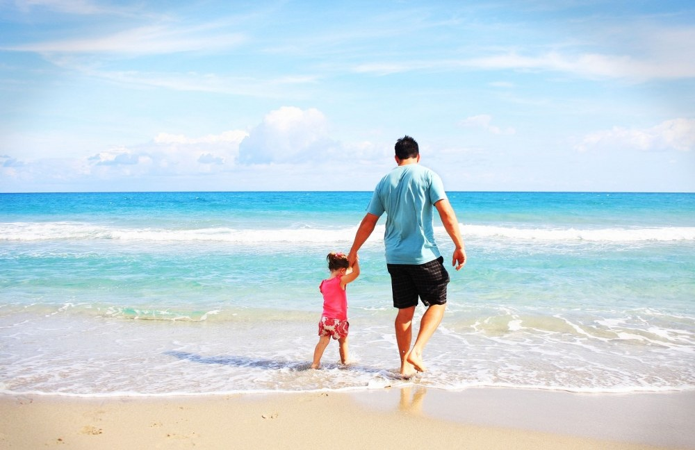 single dad holidays - dad with child on beach