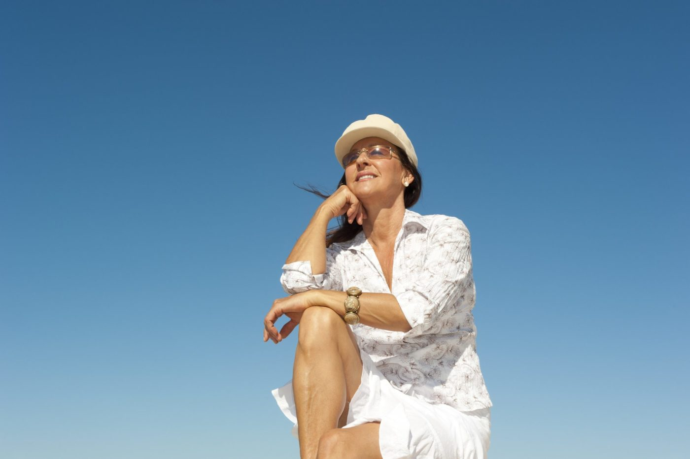 singles holidays for the over 60s - mature woman enjoying the sunshine
