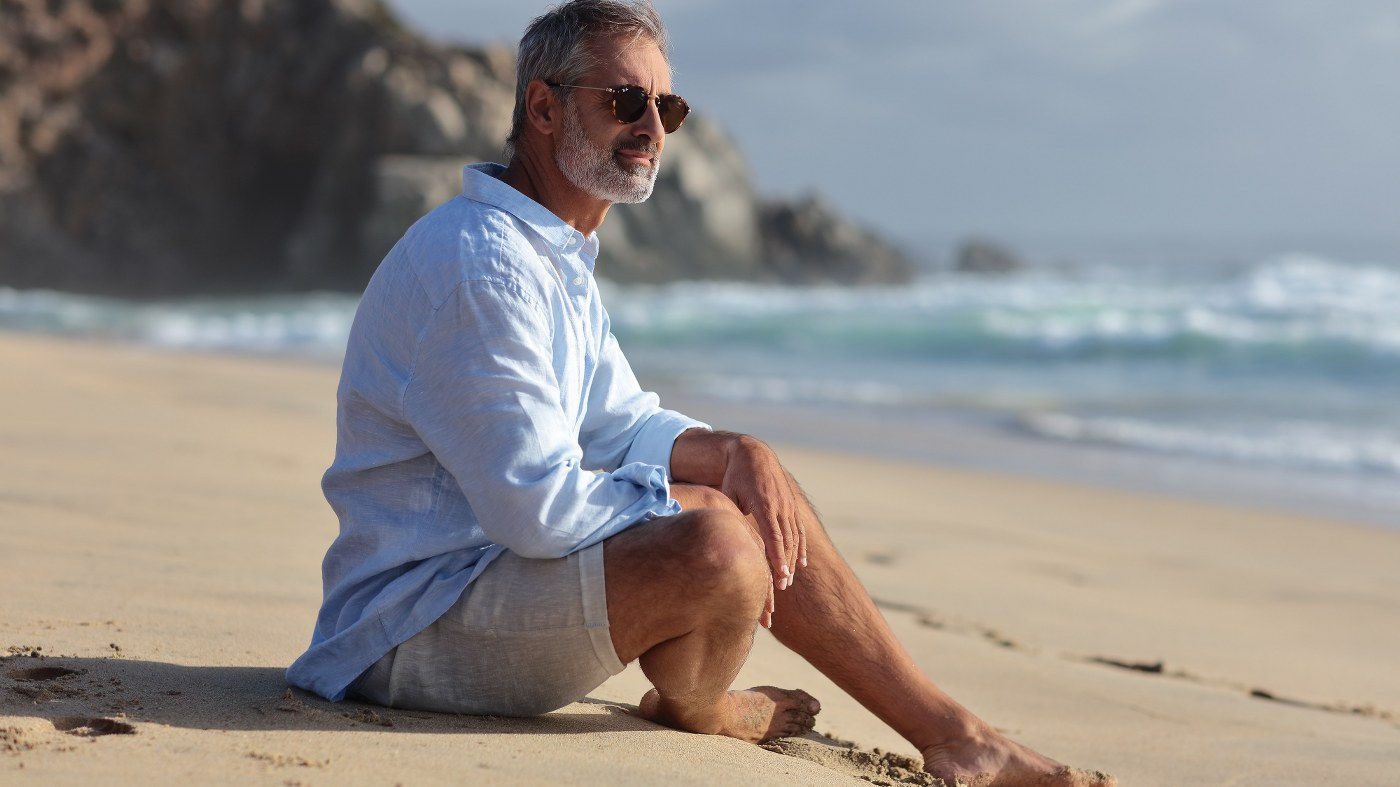 singles holidays for the over 60s - attractive 60 something man sitting on the beach