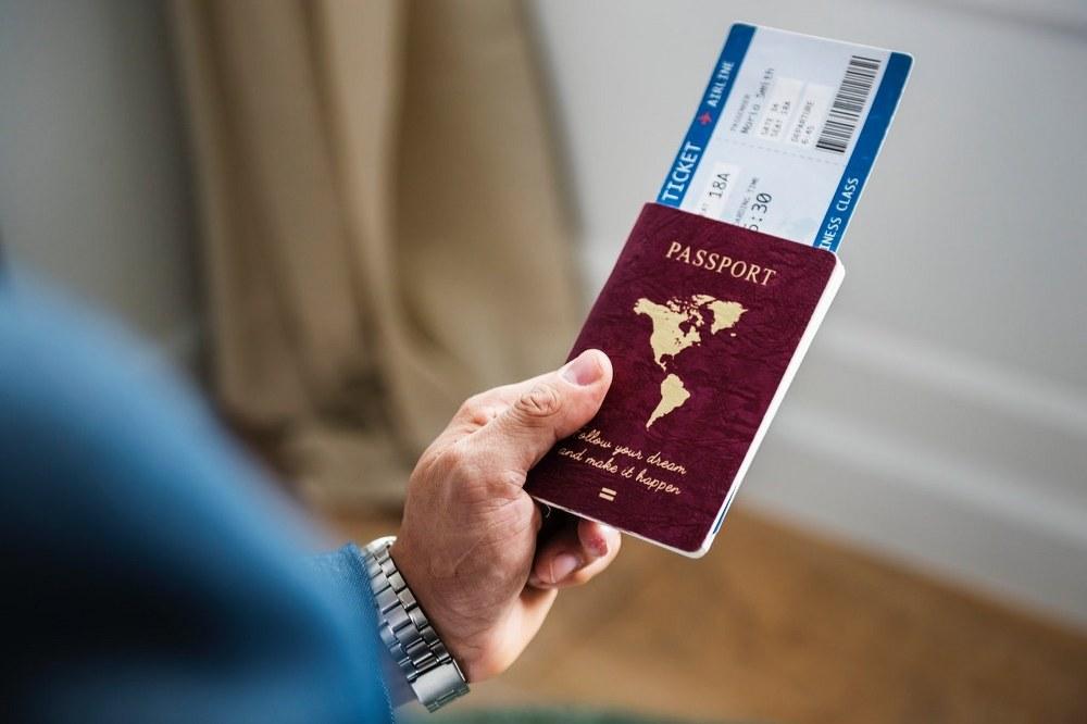 why do flight prices change - man holding passport