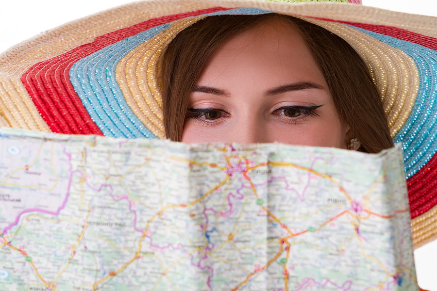 young girl wearing a sunhat reading map