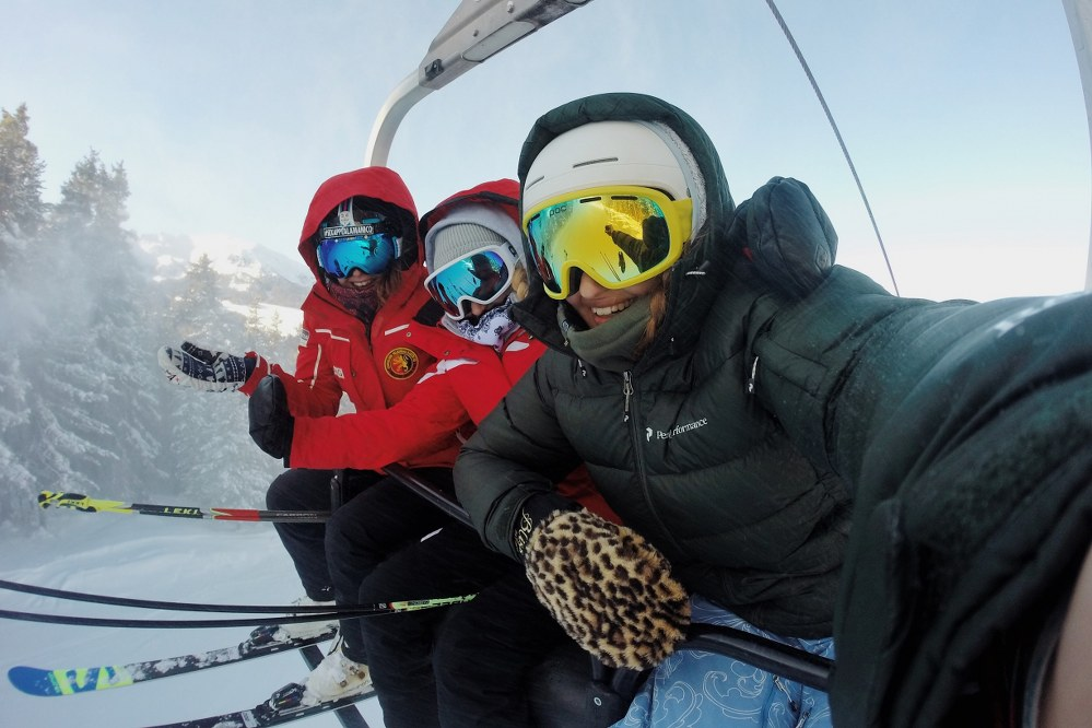 skiers on chair lift with goggles - ski holiday packing list