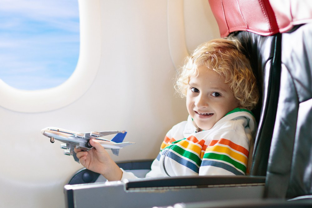 boy playing with toy plane on flight: flying with a disabled child