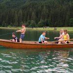 children in boat on lake