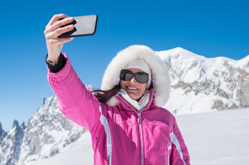 the ski holiday packing list - female skier taking selfie