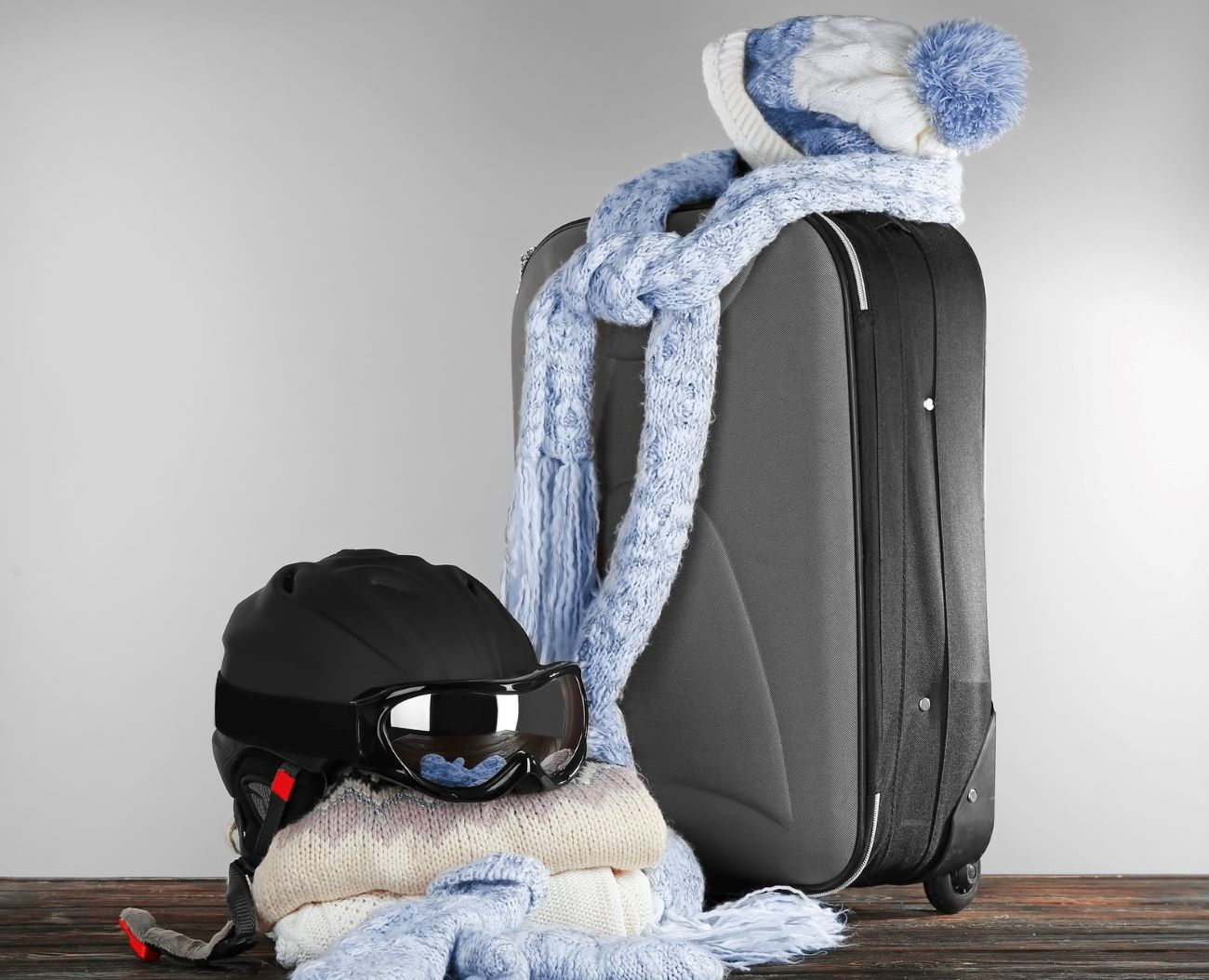 suitcase with helmet and ski clothes piled on top