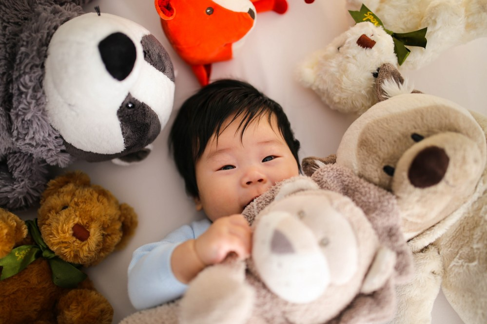 baby with lots of teddies and plush toys - cool kids bedroom
