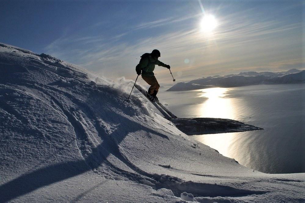 man skiing downhill on steep piste
