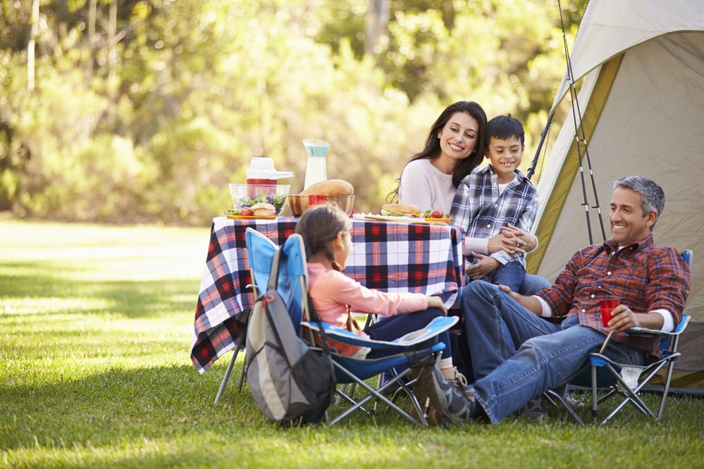 happy family outside tent on camping trip