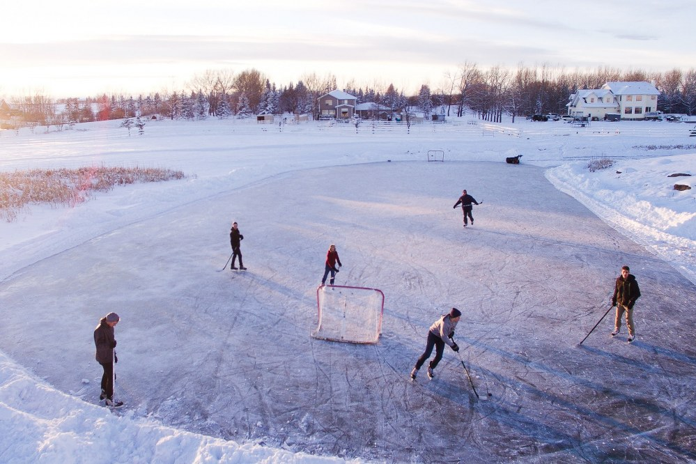adults and kids ice skating on a frozen lake