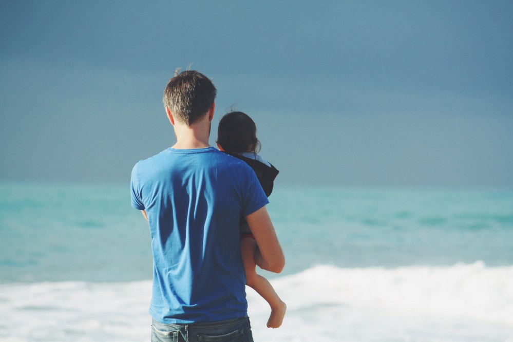 single dad and toddler with sea in background