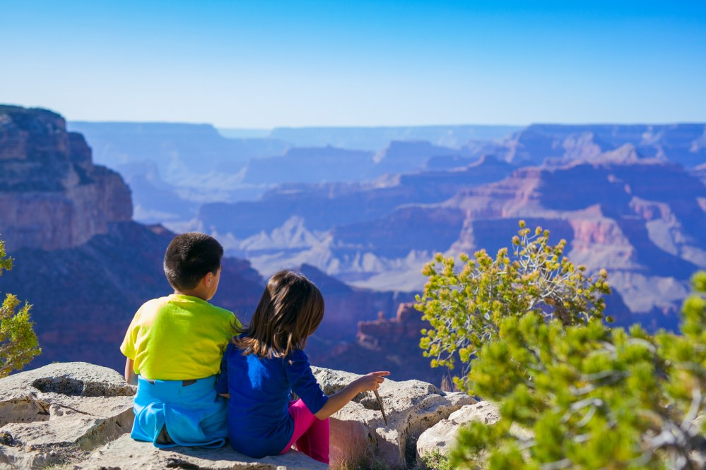 girl and boy overlooking Grand Canyon on family travel to US
