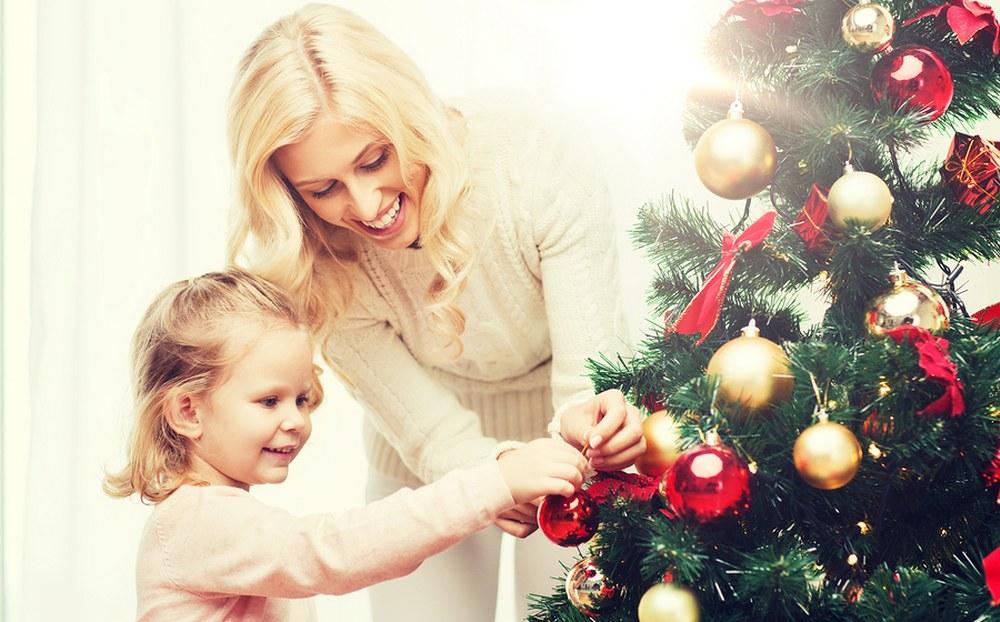 single mum and daughter decorating xmas tree