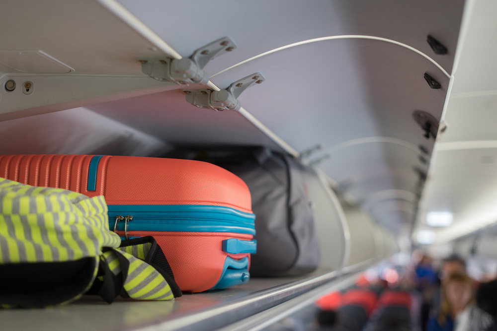 hand luggage in luggage compartment on plane