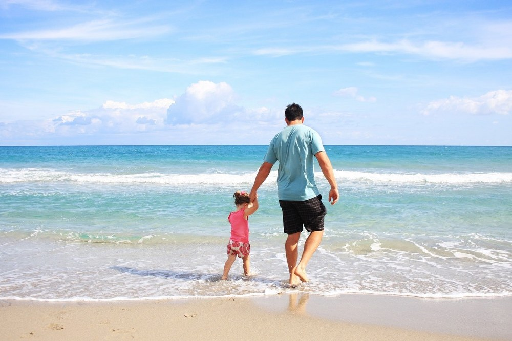 single dad and daughter on beach holiday