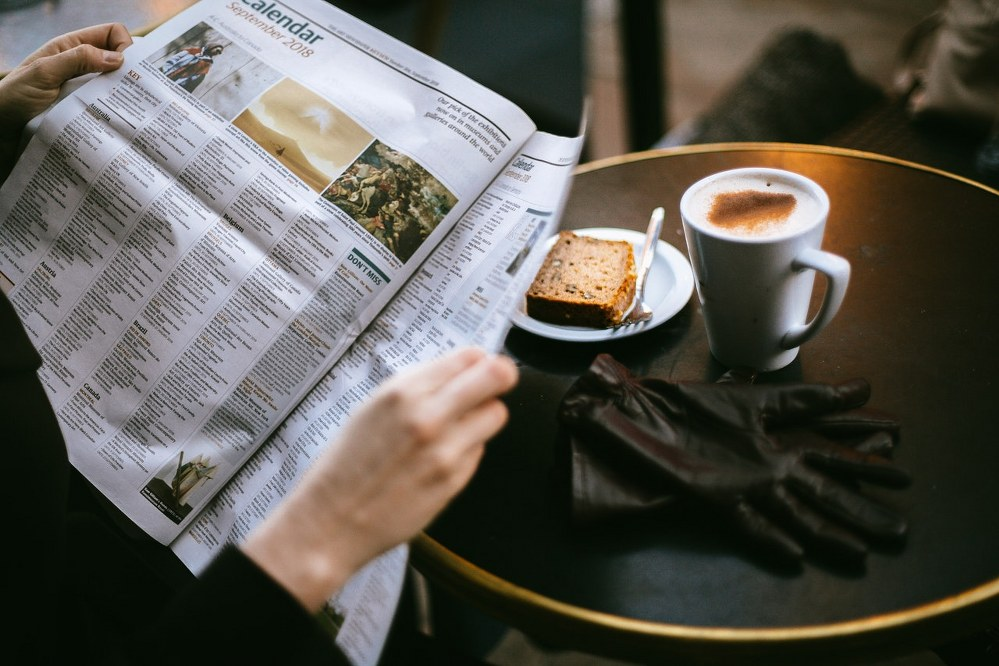 woman on solo travel reading paper and having breakfast