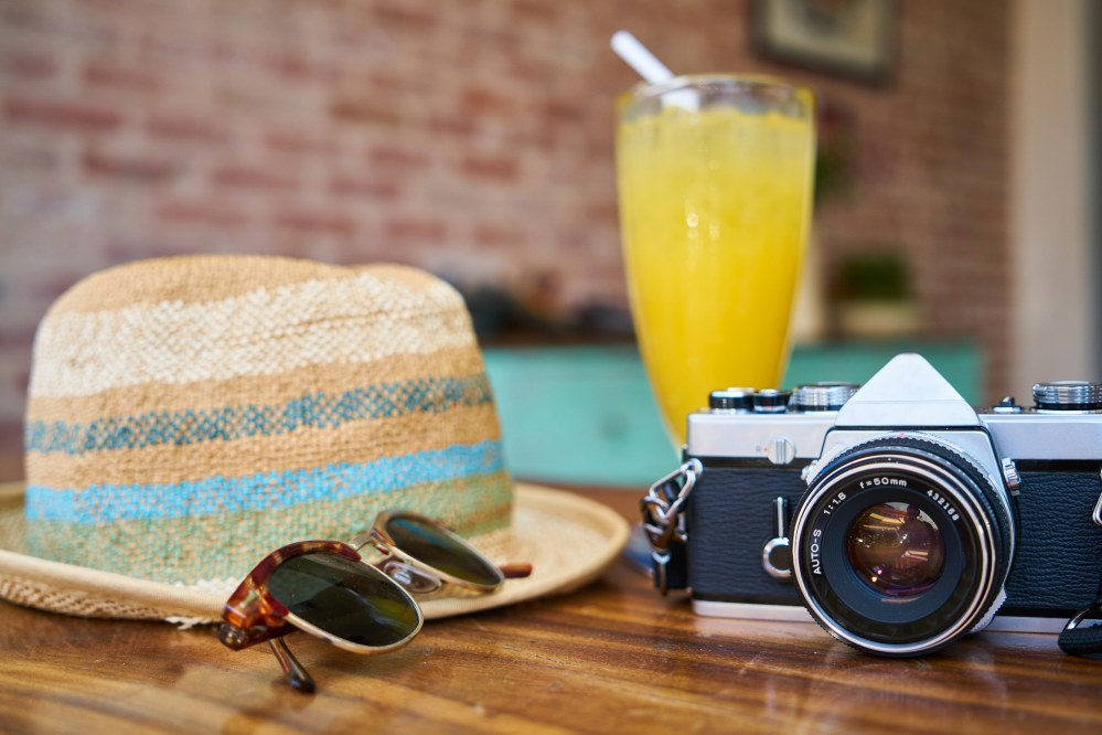 hat, sunglasses, camera: travel accessories of a sing traveller