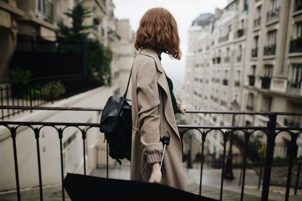 solo woman on city trip on bridge with umbrella