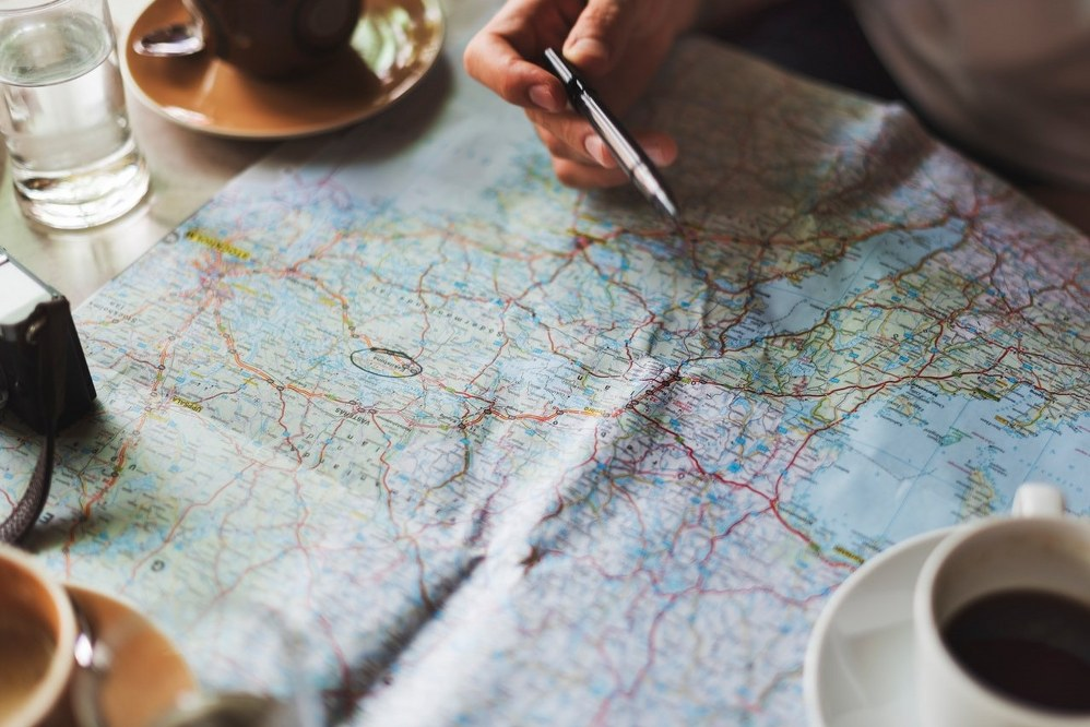 solo planning travel with map and coffee