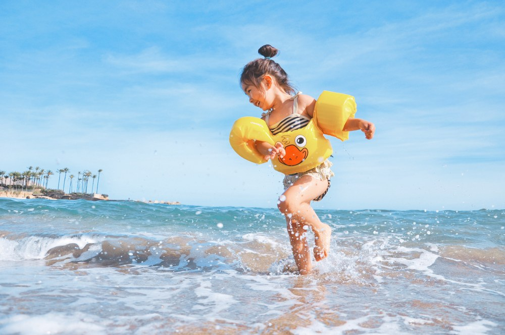 girl with armbands playing on beach on single mum holiday