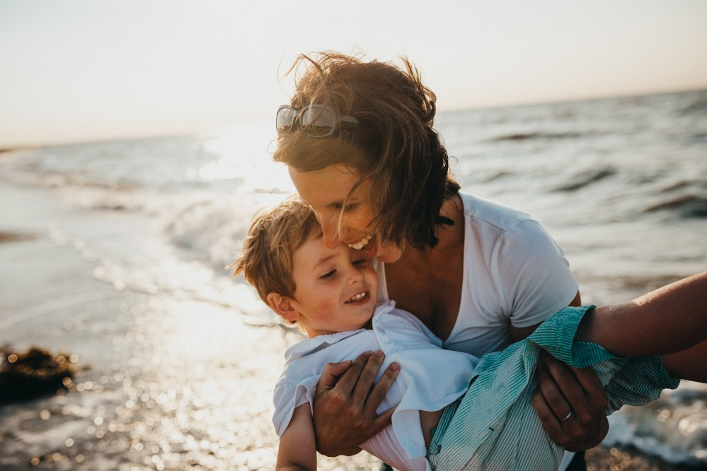 single mum and son on beach holiday