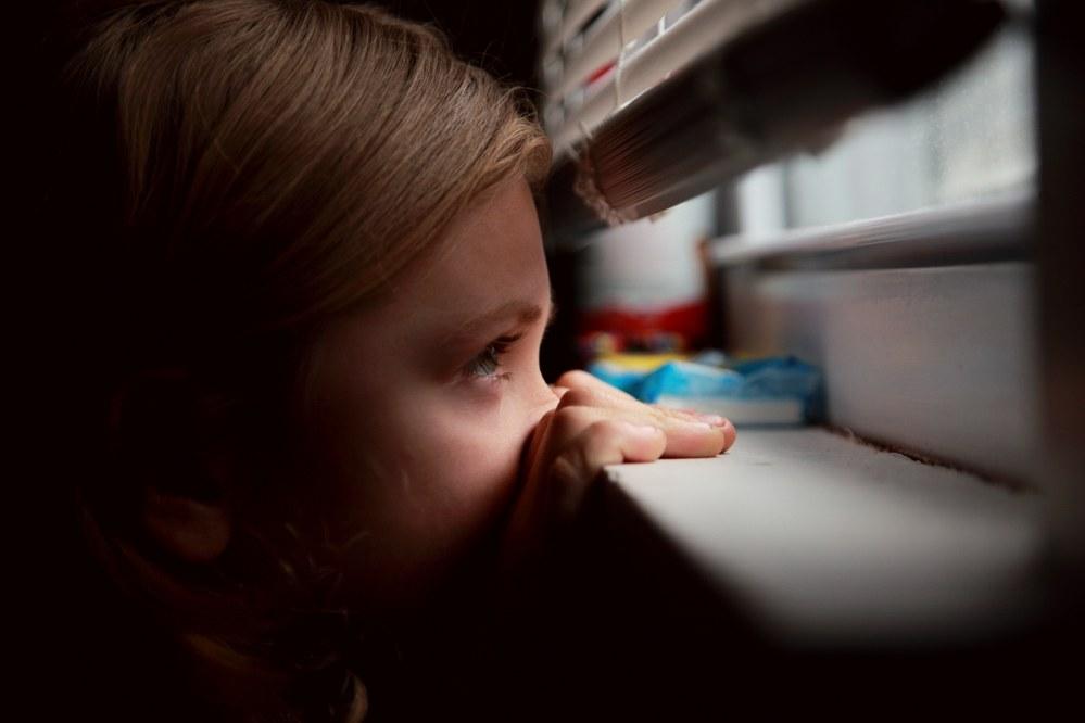 child looking out of window during Coronavirus lockdown