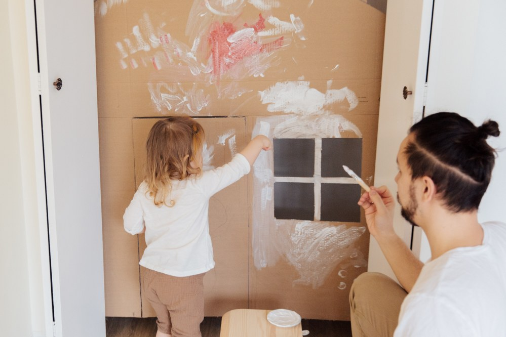 dad and daughter painting cardboard house during lockdown