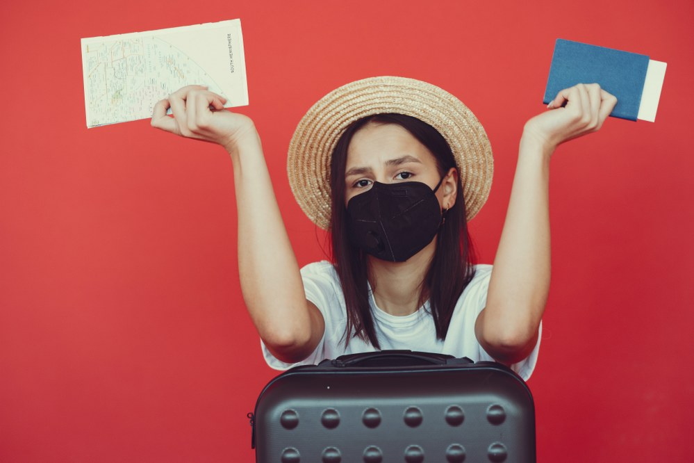 when can we travel abroad again? woman with mask and suitcase