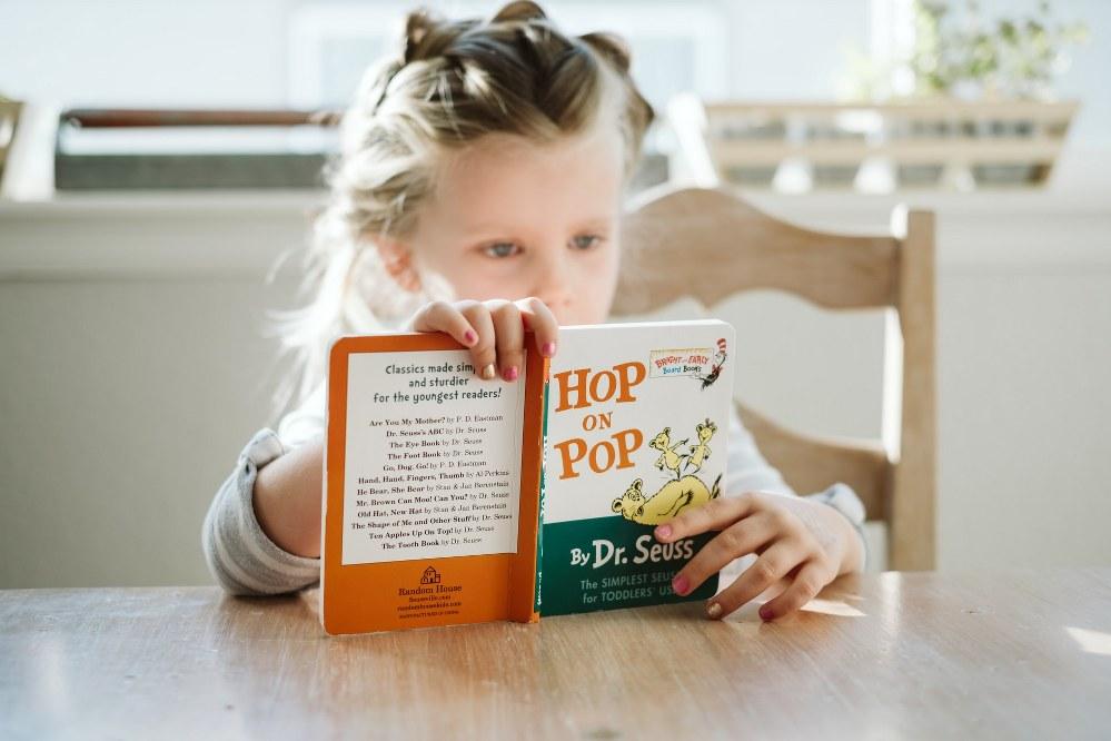 childrens books for single parents - girl reading Dr Seuss