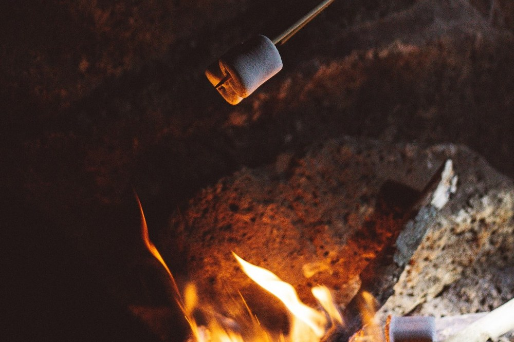 grilling marshmallows over camp fire