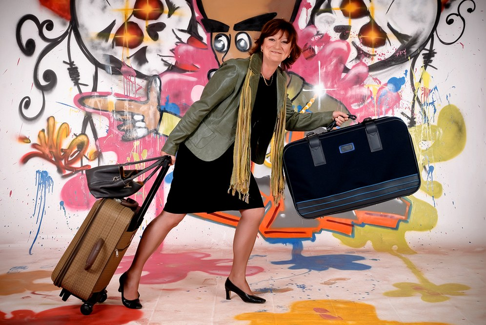 single woman in her 50s pulling suitcase on holiday