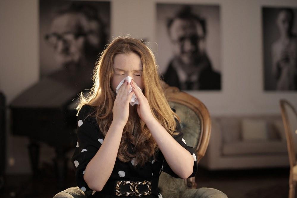 woman sneezing in tissue during coronavirus pandemic