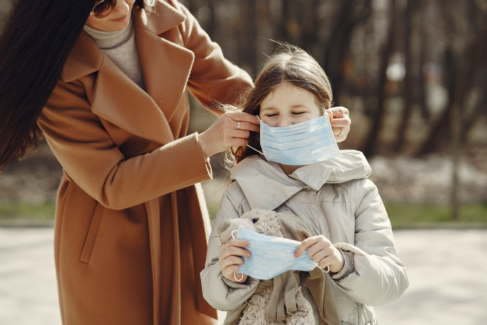 mother helping daughter with facemask during coronavirus