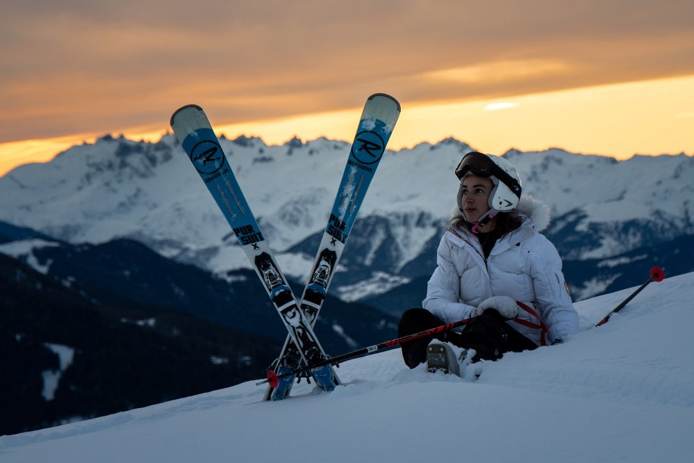 woman with Rossignol skis at sunset