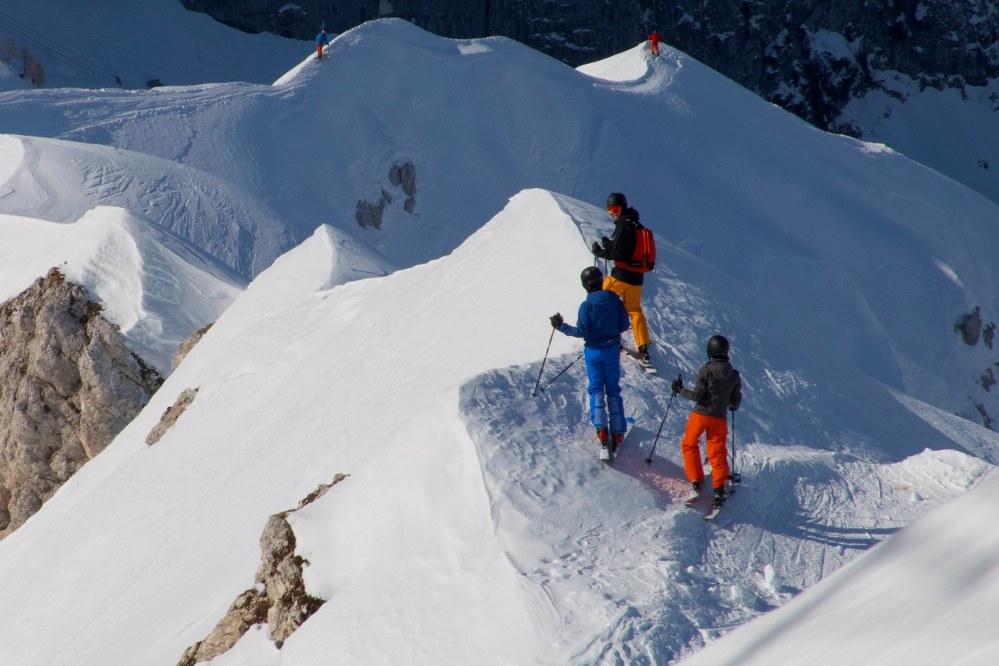 skiers on edge of steep slope