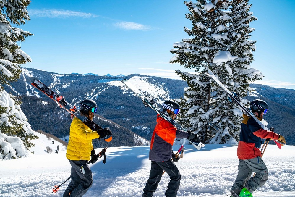 3 skiers carrying skis