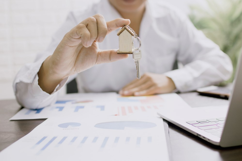 person holding miniature house calculating home insurance