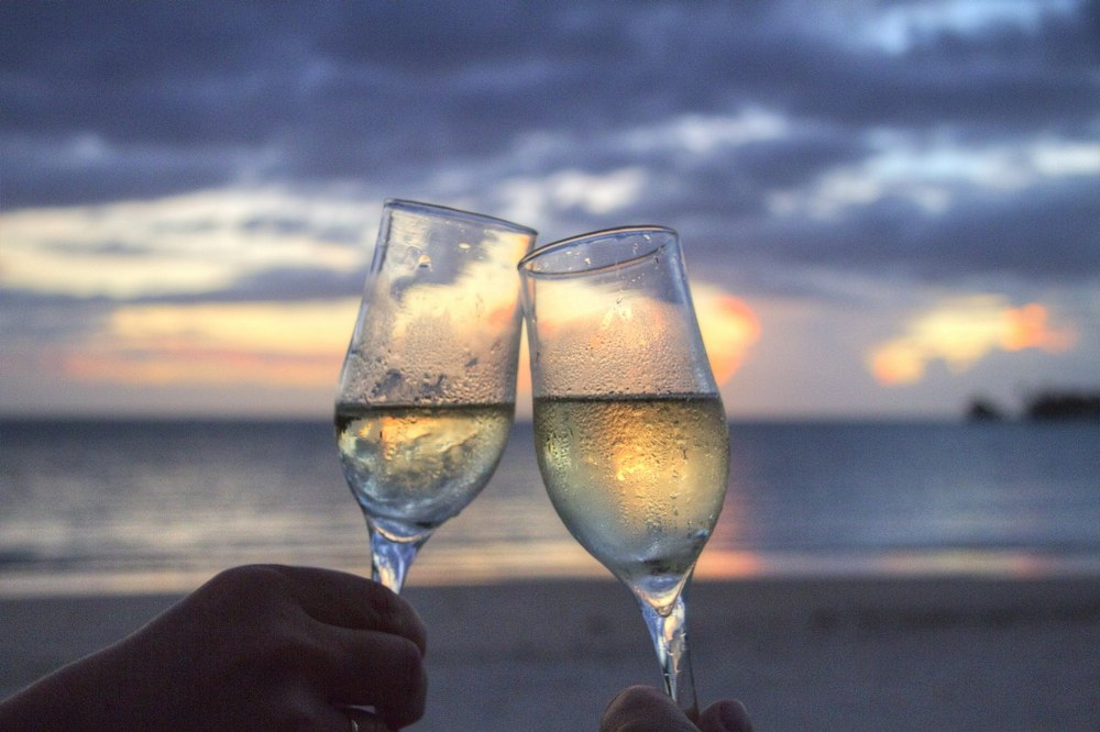 two prosecco glasses against sunset